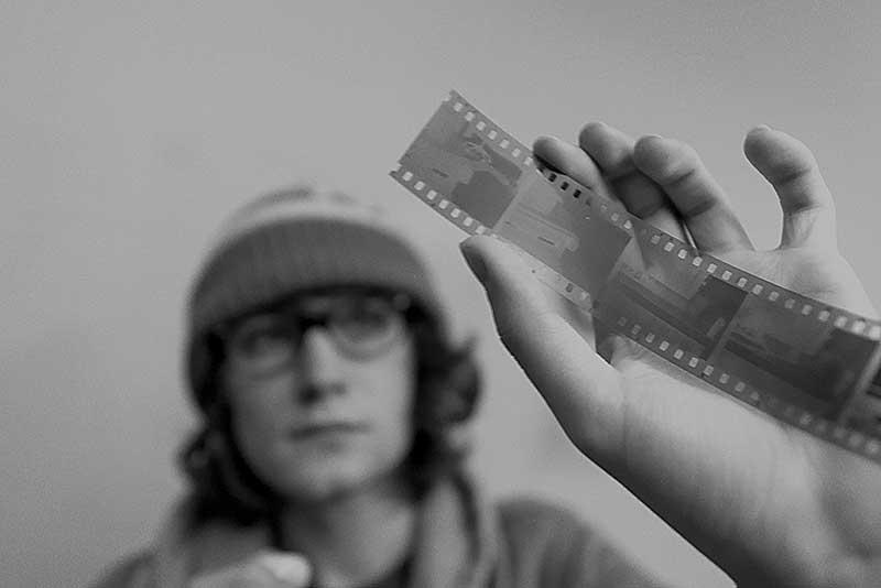 MWSU art student holding a film negative in a darkroom